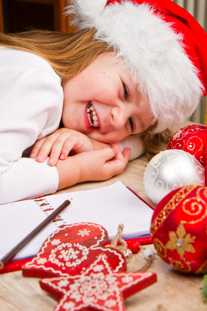 s stomach: Funny girl in Santa hat writes letter to Santa near christmas decoration