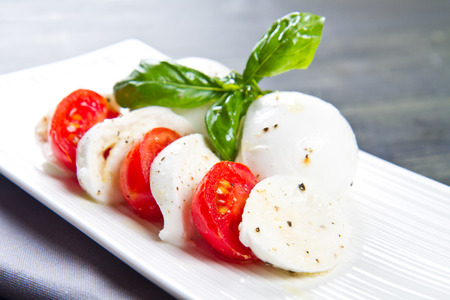 Tomato and mozzarella with basil leaves photo