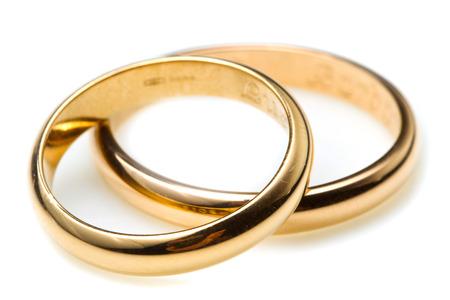 matrimonio feliz: par de anillos de bodas de oro sobre fondo blanco