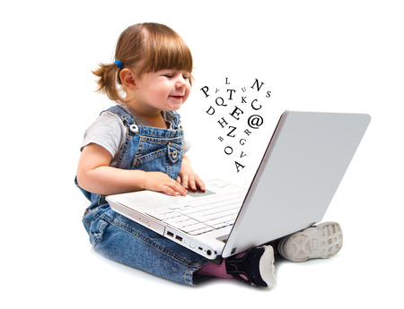 babys: Cute little girl sitting with a laptop Stock Photo