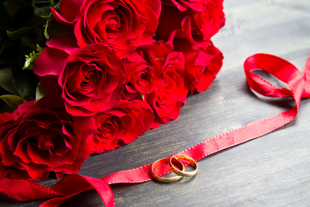 rose ring: valentine day Red roses and wedding ring a wooden background