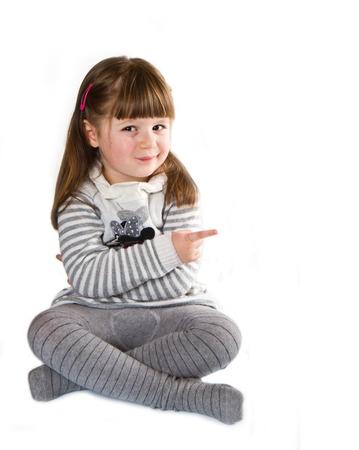 indicating: Smiling little girl indicating the something, white background