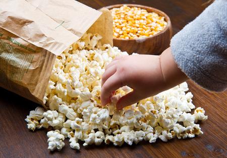 bowl of popcorn: Hands of children eating popcorn Stock Photo