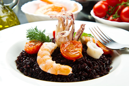 octopus: Arroz negro con calamares en rodajas, las gambas y tomate en un plato blanco Foto de archivo
