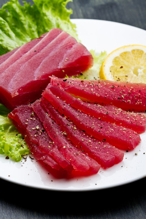 atun rojo: Rebanadas de crudo sashimi de atún rojo en el plato blanco sobre fondo de madera Foto de archivo