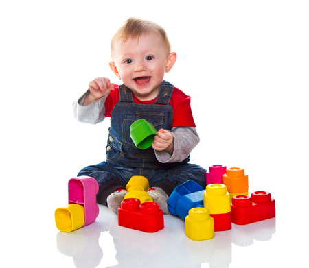 little boy playing with colored soft cube isolated on white photo