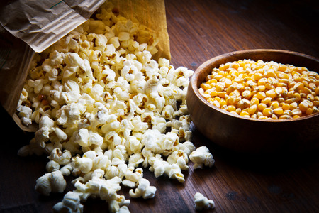 bowl of popcorn: A bowl of popcorn and kernels on a wooden table