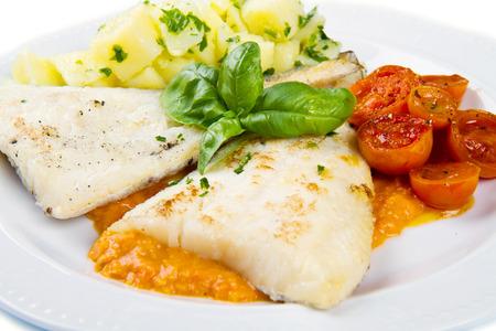 potato cod: white dish of Fresh black cod with potatoes and tomatoes sauce Stock Photo