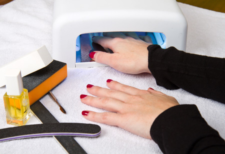 cancer foot: Hands with uv lamp for nails Stock Photo