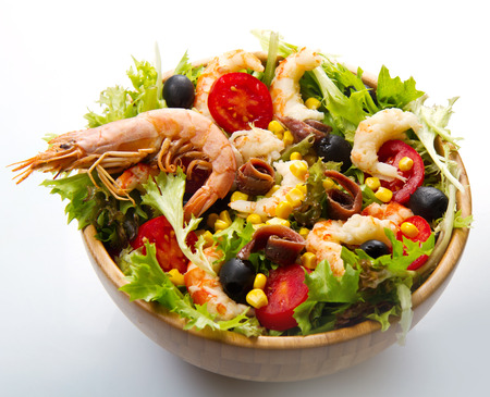 good cholesterol: salad of shrimp mixed greens black olives anchovies and tomatoes isolated on white