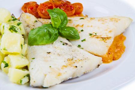plato de pescado: plato blanco de bacalao negro fresco con patatas y salsa de tomates Foto de archivo
