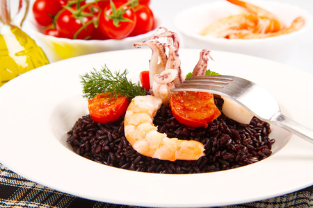 black rice with squid , prawns and tomatoes Stock Photo