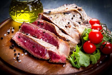 charbroiled: grilled sliced meat fillet on wooden background