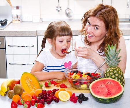 ensalada de frutas: madre da a la niña una ensalada de frutas en la cocina. Foto de archivo