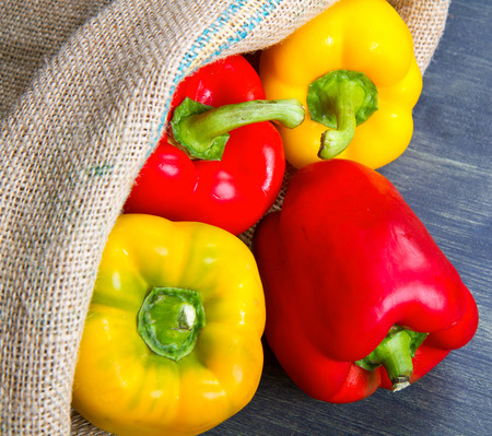 burlap sack: red and yellow pepper on burlap sack on wooden Stock Photo