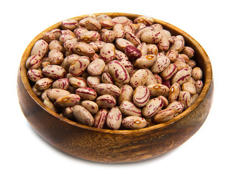 pinto beans: pinto beans on wood bowl isolated on white