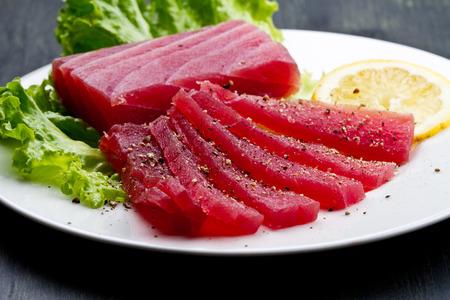 atun rojo: Rebanadas de crudo sashimi de at�n rojo en el plato blanco sobre fondo de madera Foto de archivo