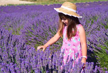 lavanda: Smiling girl sniffing flowers in a lavender field