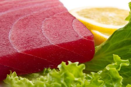 atun rojo: tuna sashimi with salad and lemon on white  Foto de archivo