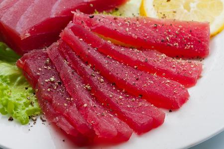 plato de pescado: Rebanadas de crudo sashimi de atún rojo en el plato blanco