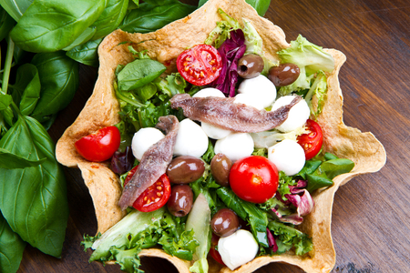 canasta de pan: ensalada mixta con queso mozzarella y anchoas en una cesta de pan