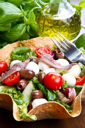 bread basket: ensalada mixta con queso mozzarella y anchoas en una cesta de pan