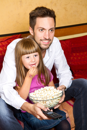 brothers and sisters: Little girl and her borther enjoy eating popcorn and watching tv at home