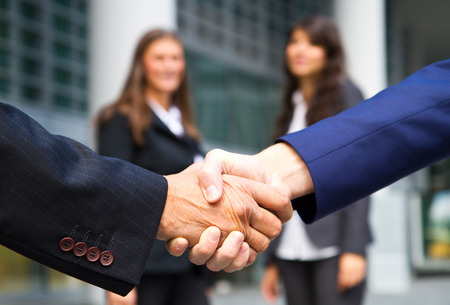 partnership power: Business handshake and business people Stock Photo