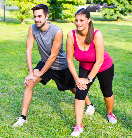 athletic wear: smiling couple doing streching in the park