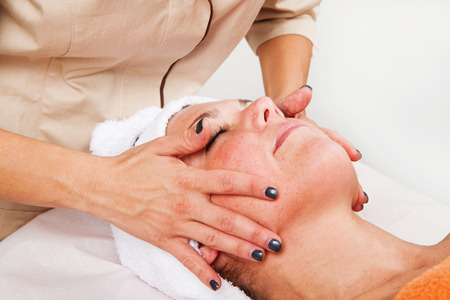 beauty center: Beautiful young woman receiving facial massage with closed eyes in a beauty center Stock Photo
