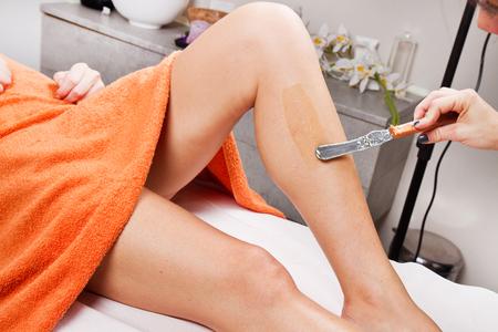 depilacion con cera: Esteticista depilación pierna de una mujer que aplica una tira de material sobre la cera caliente para eliminar los pelos