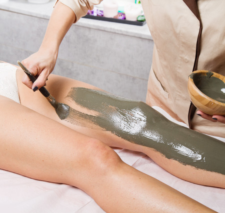 hand care: relaxing woman lying on a massage table receiving a mud treatment Stock Photo