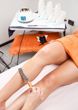 therapeutical: Beautician waxing a womans leg applying a strip of material over the hot wax to remove the hairs