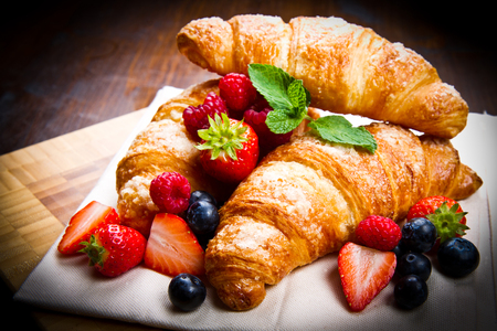 sweet pastries: Fresh tasty croissants with berries on wooden background Stock Photo