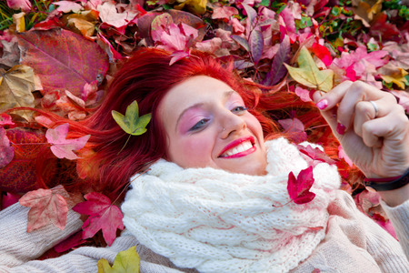 lying on leaves: beautiful woman lying on autumn leaves Stock Photo