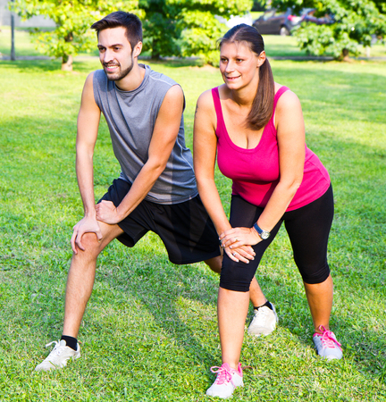 women sport: smiling couple doing streching in the park
