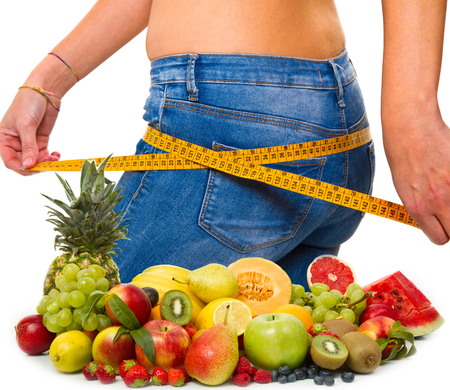 slim girl: a slender young woman in jeans with a tape measure after a successful diet