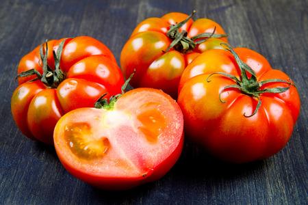 tomates: beefsteak tomates, aislados en la madera