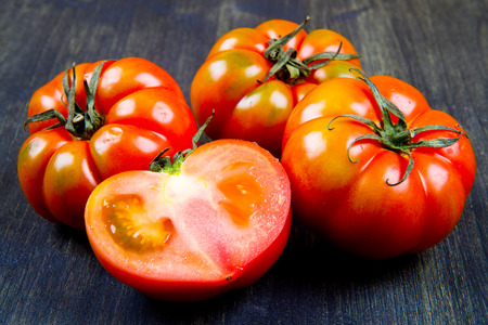 Beefsteak tomatoes, isolated on wood