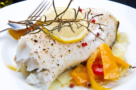 prepared dish: white baked cod with pepper and rosemary Stock Photo