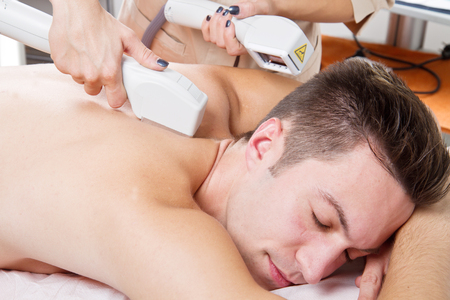 male hair: young man receiving laser epilation on beauty center