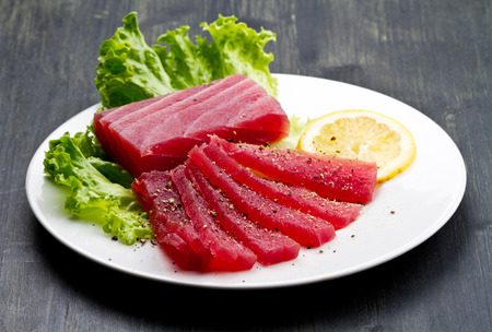 Slices of raw bluefin tuna sashimi on white dish on wood background