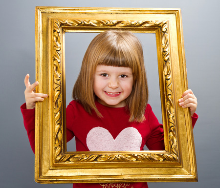 looking through frame: smiling girl looking through a vintage picture frame