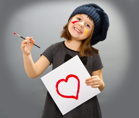 painter girl: little painter girl with a drwan heart isolated on grey Stock Photo