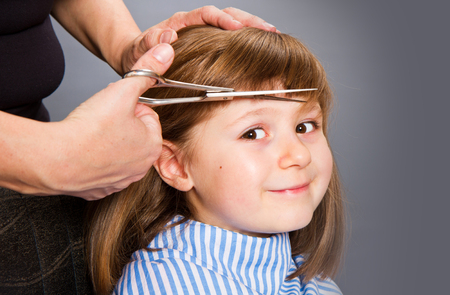 Hairdresser making a hair style to cute little girl