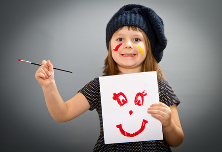 painter girl: little painter girl with a drwan smile isolated on grey Stock Photo