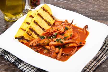 polenta: fish soup with grilled polenta on white dish