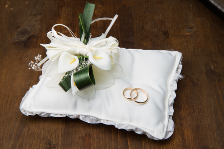 anillos boda: Los anillos de boda con el ramo de cala en el fondo de madera