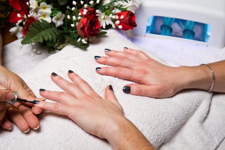 cancer foot: manicure and Hands with uv lamp for nails Stock Photo