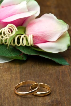 anillos boda: anillos de bodas con rosas de color rosa sobre fondo de madera